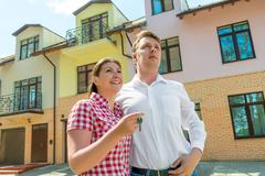 Happy couple with the keys in the hands about his new townhouse Stock Photos