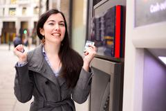young woman celebrating at the cash machine - stock photo