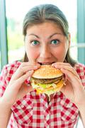 Hungry girl holding hands a hamburger - stock photo