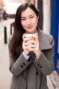 Young woman holding a take away coffee Stock Photos