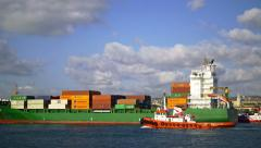 A cargo ship laden with shipping containers slowly sails out seaport Stock Footage