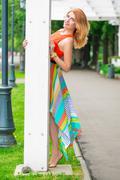 beautiful girl peeping from behind pillar gazebo in the park - stock photo
