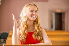 Girl at the desk with a raised hand is ready to answer a lesson Stock Photos