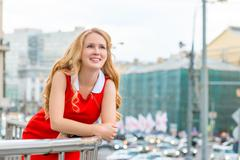 Portrait of a blonde leaning on the balcony railing against the backdrop of t Stock Photos