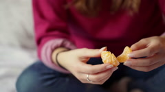 Girl sitting cross-legged on the bed and eating mandarine, steadycam shot Stock Footage