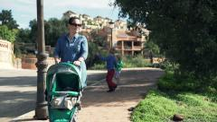 Young mother walking with her baby in city Stock Footage