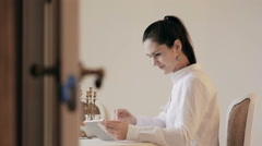 Close shot Woman using tablet and drinking coffee by table Stock Footage