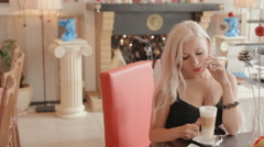 Sexy blonde having breakfast in a cafe with latte and dessert Stock Footage