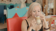 Charming blue-eyed blonde drinking latte in cafe Stock Footage