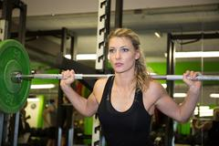 Strong woman lifting barbell as a part of crossfit exercise routine. - stock photo