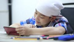 Little asian boy looking cellphone and drawing . - stock footage