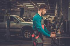 Specialist near car diagnostic pc in a workshop Stock Photos