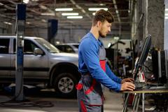 Stock Photo of Specialist near car diagnostic pc in a workshop