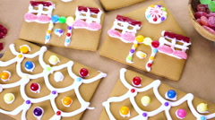 Decorating gingerbread house with royal icing and colorful candies. Stock Footage