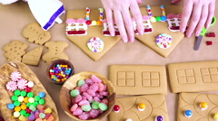 Stock Video Footage of Girl making gingerbread house with royal icing and colorful candies.