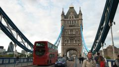 Red double decker buses pass on the tower bridge, london Stock Footage