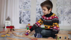 Adorable little preschool boy, playing with wooden trains and railroad at hom Stock Footage