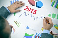 businessman observing a chart with an upward trend during 2015 - stock photo