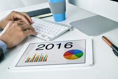 Man with the economic forecast for 2016 in his tablet Stock Photos