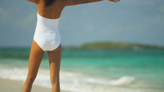 Latin American girl in swimsuit walking barefoot by a tropical ocean Stock Footage