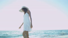 Ethnic Hispanic female in white sun dress on vacation ocean beach - stock footage