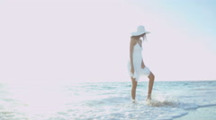 Latin American girl walking barefoot by tropical ocean Stock Footage
