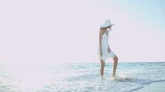 Latin American girl walking barefoot by tropical ocean Stock Footage