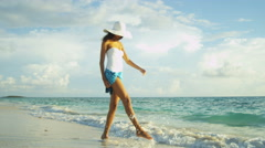 Carefree Latin American girl wearing swimsuit and sunhat at luxury beach resort - stock footage