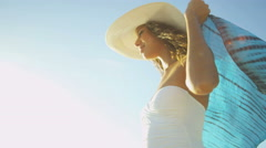 Latin American girl in swimsuit and sunhat by a tropical ocean - stock footage