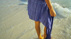 Legs of barefoot Latin American female in sarong on vacation beach Stock Footage