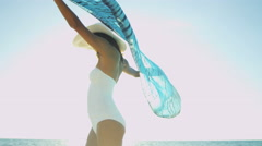 Young Latin American girl in swimsuit barefoot on tropical beach - stock footage