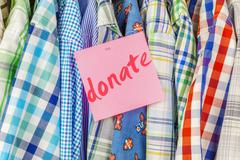 Stock Photo of Row of hanging shirts with inscription donate on paper note