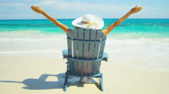 Young ethnic girl sunbathing in a beach chair on a tropical beach - stock footage