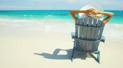 Beautiful Hispanic girl sunbathing in a bikini and sunhat on beach - stock footage