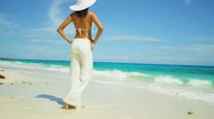 Latin American girl in bikini top and beach trousers barefoot by tropical ocean - stock footage