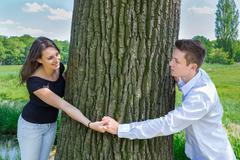 Young attractive caucasian couple in love holding hands around tree trunk - stock photo