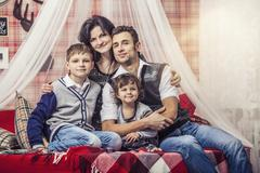 Family mum dad and kids together at home in the cosy atmosphere of the bedroo - stock photo