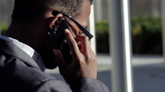 outdoor black businessman having a phone call using a cell phone - stock footage