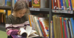 Girl Sits On The Floor Near The Bookshelves And Leafs Through The Book Grey Stock Footage