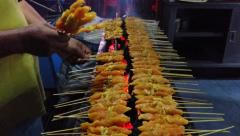 A street hawker is selling delicious, sizzling satay. Stock Footage