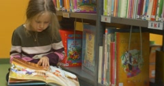 Little Girl In Striped Sweater Sits On The Floor Near The Bookshelves And Leafs - stock footage