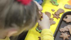 Little happy girl decorates gingerbread cookies Stock Footage