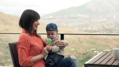 Young, happy mother playing with her child with toy on terrace Stock Footage