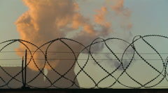 Smoking Chimney behind Barbed Wire - stock footage