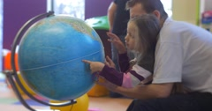 Little Blonde Girl With Long Hairs Kid With Her Father are Sitting at a Globe - stock footage