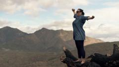 Happy woman stretching arms and admire view while standing on trunk Stock Footage