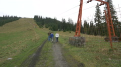 Tourists passing by a mountain chairlift system, heading to Horses Waterfall Stock Footage