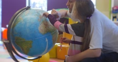 Little Blonde Girl Kid is Standing at a Globe Father is Rotating the Sphere Stock Footage