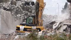 A huge excavator with hydraulic jackhammer crashes reinforced concrete Stock Footage
