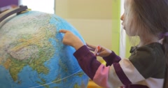 Little Blonde Girl With Long Hairs Kid is Standing at a Globe Rotating the Stock Footage